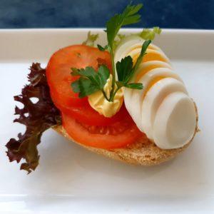 Rundstykke med egg og tomat.